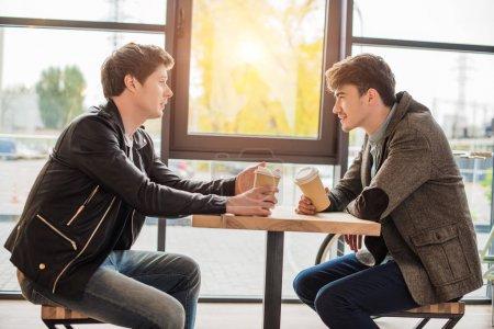 Foto de Dos jóvenes sentados con un café en un café y conversación - Imagen libre de derechos