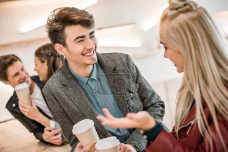 Photo for Two heterosexual couples talking at the wooden bar counter - Royalty Free Image