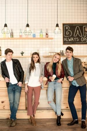Photo for Young men and women standing at bar counter and posing to the camera - Royalty Free Image