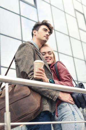 Photo for Lovely couple hugging and standing outside with coffee in paper cup - Royalty Free Image