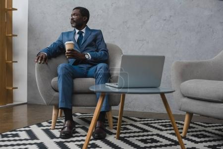 Photo for Middle aged businessman sitting with a coffee in paper cup and looking away - Royalty Free Image