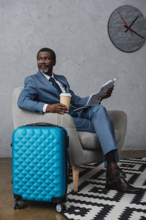 Photo for African american man reading newspaper and holding coffee in a paper cup - Royalty Free Image