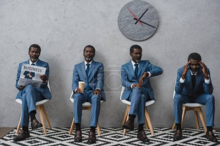 Photo for Businessmen waiting at reception, same man in different poses - Royalty Free Image