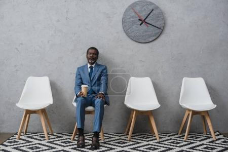 Photo for Handsome African american businessman sitting in a waiting room and holding coffee in a paper cup - Royalty Free Image