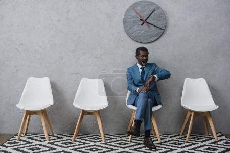 Photo for Handsome African american businessman sitting in a waiting room and looking at watch - Royalty Free Image