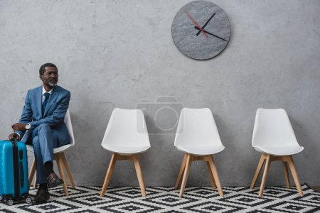 Photo for Handsome businessman sitting in a waiting room with suitcase - Royalty Free Image