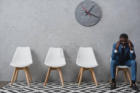 Photo pour Fatigué homme assis dans une salle d'attente et de toucher la tête avec les mains, avoir des maux de tête - image libre de droit