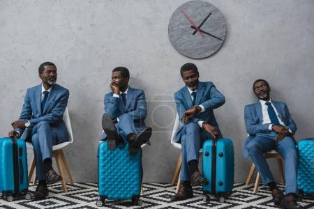 Photo for Businessmen sitting in a waiting room with suitcases, same man in different poses - Royalty Free Image