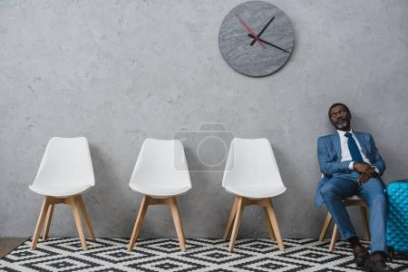 Photo for Handsome African american businessman napping in a waiting room - Royalty Free Image