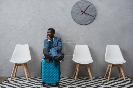 Photo for Handsome African american businessman sitting in a waiting room putting legs on suitcase - Royalty Free Image