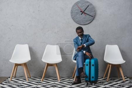 Foto de Empresario americano africano guapo sentado en una sala de espera con maleta y mirando el reloj - Imagen libre de derechos