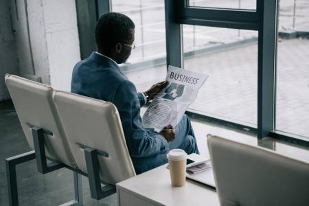 Journal de lecture homme d'affaires à l'aéroport