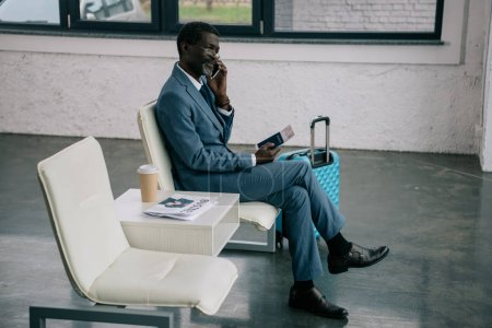 Businessman talking by smartphone in airport