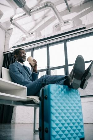 Photo for Middle aged African american businessman waiting at airport putting legs on suitcase and drinking coffee - Royalty Free Image