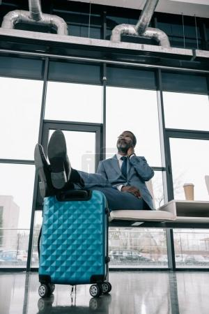 Middle aged African american businessman waiting at airport and putting legs on suitcase