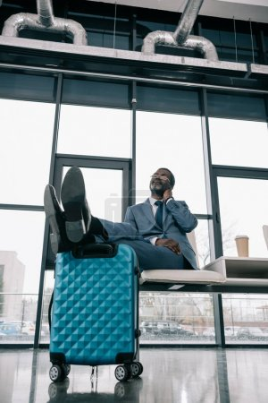 Photo for Middle aged African american businessman waiting at airport and putting legs on suitcase - Royalty Free Image