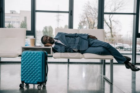 Photo for Middle aged African american businessman napping on chairs at airport - Royalty Free Image