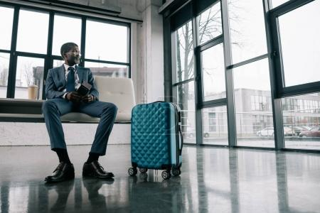 Photo for Middle aged African american man in suit waiting for a flight at the airport - Royalty Free Image