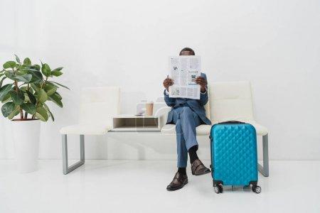 Photo pour Homme d'affaires américain assis dans la salle d'attente et la lecture des journaux - image libre de droit