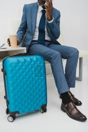 Photo for Cropped image of middle aged man talking by smartphone while waiting at the airport - Royalty Free Image