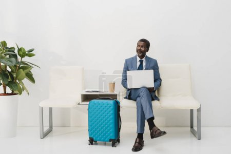 Photo for Middle aged African american businessman working with a laptop while waiting at the airport - Royalty Free Image
