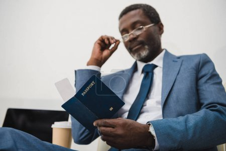 Photo for Middle aged African american businessman sitting at airport and checking departure time in the ticket - Royalty Free Image