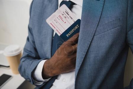Man hiding passport and ticket in suit