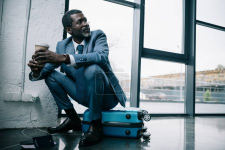 Photo for Middle aged African american businessman sitting on a suitcase at the airport and holding coffee - Royalty Free Image