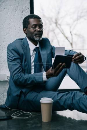 Foto de Medio de años hombre de negocios sentado en un piso en el aeropuerto y mirando el pasaporte - Imagen libre de derechos