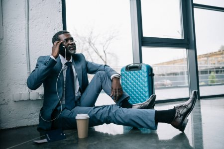 Photo for Middle aged African american businessman sitting on a floor at the airport and talking by smartphone - Royalty Free Image