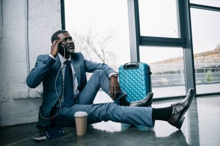 Foto de Medio de años hombre de negocios afroamericano sentada en un piso en el aeropuerto y hablando por teléfono inteligente - Imagen libre de derechos