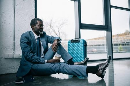 Photo for Middle aged African american businessman sitting on a floor at the airport and looking at watch - Royalty Free Image