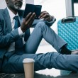 businessman sitting on floor at airport