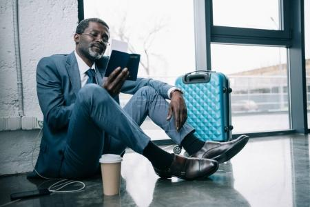 Photo for Middle aged African american businessman sitting on a floor at the airport and looking at passport - Royalty Free Image