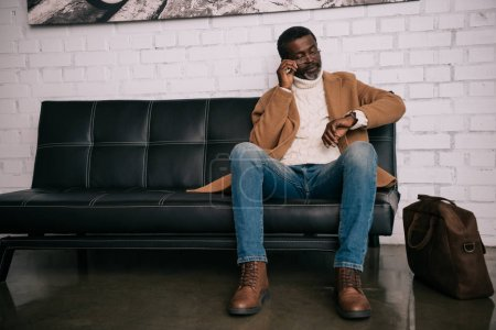 Man looking above glasses at watch