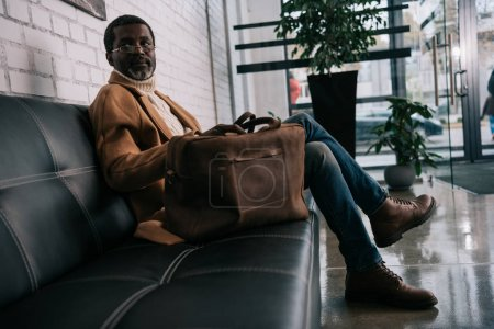 Photo for Middle aged traveler sitting on a sofa and waiting for departure with a baggage - Royalty Free Image