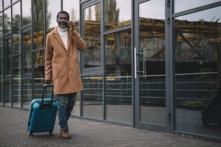 Foto de Medio de años hombre caminando en una calle con una bolsa con ruedas y hablando por teléfono inteligente - Imagen libre de derechos