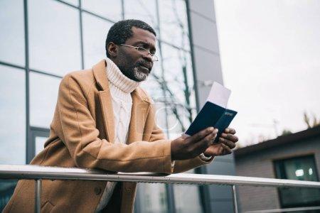 homme debout avec billet passeport et mouche