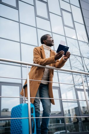 man standing with passport and fly ticket