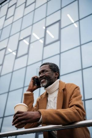 Photo for African american man talking by smartphone, smiling and standing with a coffee in a paper cup - Royalty Free Image