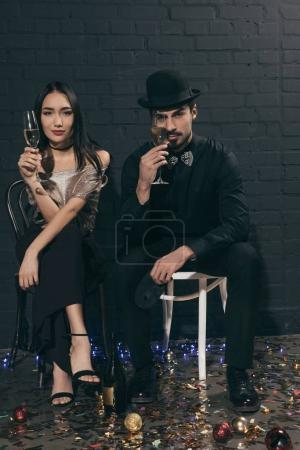 stylish multicultural couple with glasses of champagne