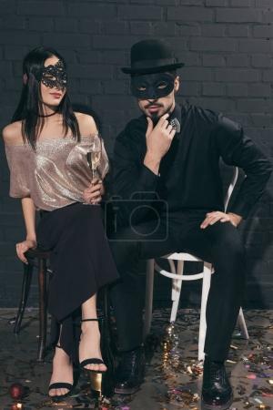 Photo pour Élégant couple multiethnique dans les masques de Noël à la nouvelle fête de l'année - image libre de droit