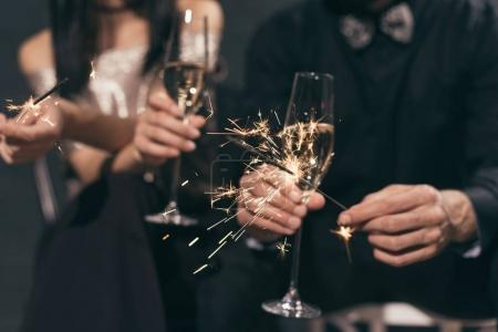 Photo for Selective focus of couple with glasses of champagne and sparkles at christmas party - Royalty Free Image
