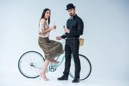 Photo pour À la mode couple multiculturel avec des verres de champagne et vélo isolé sur blanc - image libre de droit