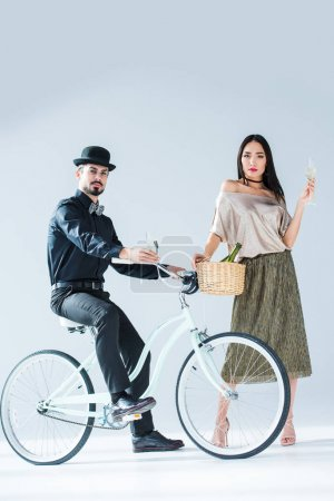 Fashionable multicultural couple with glasses of champagne and retro bicycle isolated on white