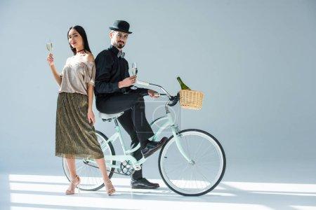 Foto de Moda multicultural pareja con gafas de champán y retra bicicleta - Imagen libre de derechos