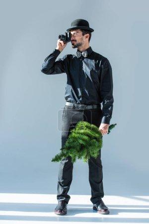man with photo camera and christmas tree