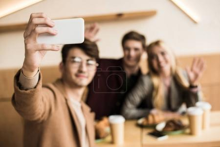 Photo for Young man taking selfie of him and friends in a cafe - Royalty Free Image