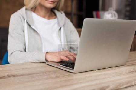 Photo for Cropped shot of woman using laptop at home - Royalty Free Image