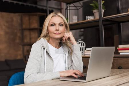 Photo for Pensive middle aged woman using laptop at home - Royalty Free Image